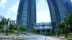 Le torri gemelle di Petronas con la fontana alla parte anteriore Kuala Lumpur, Malesia stock footage