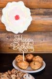 Le torte di compleanno ed i muffin con il saluto di legno firmano su fondo rustico Di legno canti con il buon compleanno delle le Immagine Stock Libera da Diritti