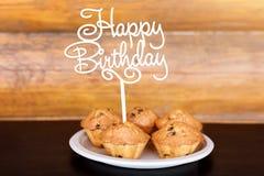 Le torte di compleanno ed i muffin con il saluto di legno firmano su fondo rustico Di legno canti con il buon compleanno delle le Immagini Stock Libere da Diritti