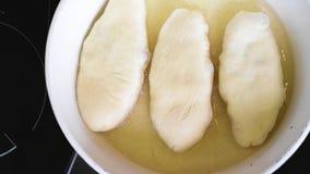 Le torte sono fritte in olio vegetale in una pentola bianca archivi video