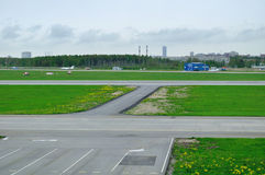 Le tour de la route de piste d'atterrissage d'aéroport avec les signaux horizontaux jaunes blancs peints Photos stock