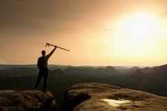 Le touriste avec des poteaux dans des mains se tiennent sur la roche observant pour la prochaine étape Source ensoleillée Images libres de droits