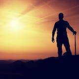 Le touriste avec des poteaux dans des mains se tiennent sur la roche observant pour la prochaine étape Source ensoleillée Images stock