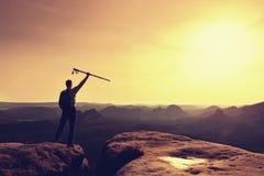 Le touriste avec des poteaux dans des mains se tiennent sur la roche observant pour la prochaine étape Source ensoleillée Photo libre de droits