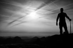 Le touriste avec des poteaux dans des mains se tiennent sur la roche observant pour la prochaine étape Source ensoleillée Image libre de droits