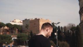 Le touriste d'homme se tient chez Colosseum à Rome, Italie Le mâle beau prend le smartphone, sert l'Internet Mouvement lent banque de vidéos