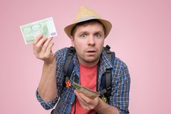 Le touriste dans le chapeau tient l'euro billet de banque le vérifiant photo libre de droits