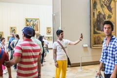Le touriste de jeune homme prend le selfie dans la galerie dans le Louvre Image stock