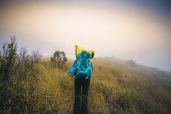 Le touriste de l'Asie de jeune homme de filtre d'Instagram à la montagne observe au cours du matin brumeux et brumeux image stock