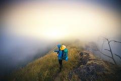 Le touriste de l'Asie de jeune homme de filtre d'Instagram à la montagne observe au cours du matin brumeux et brumeux photos libres de droits