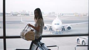 Le touriste féminin européen marche à la fenêtre terminale de salon d'aéroport, met son sac vers le bas et regarde le dépassement banque de vidéos