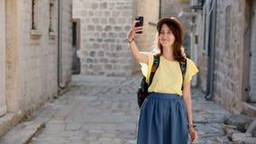 Le touriste féminin gai dans le chapeau, font une photo sur le dispositif moderne de téléphone portable marchant sur des rues Voy clips vidéos