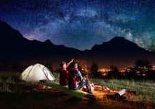 Le touriste féminin montre sur le ciel étoilé et le chemin laiteux Images stock