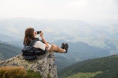 Le touriste féminin prend la photo des jambes avec le téléphone portable à partir du dessus de la falaise de montagne Photos stock