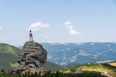 Le touriste féminin tient le dessus de la roche dans le secteur de montagne et regarde le beau paysage panoramique Photographie stock