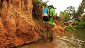 Le touriste marche en rivière Genou-profonde de Fée-courant par des roches banque de vidéos