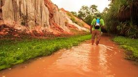 Le touriste marche le long des eaux rouges du Fée-courant par des paumes de roches clips vidéos