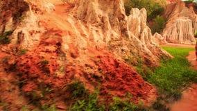 Le touriste marche le long des eaux rouges par des photos de roches de Fée-courant banque de vidéos