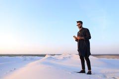 Le touriste masculin musulman parle du téléphone et partage des actualités, se tenant dedans Photos stock
