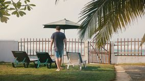Le touriste masculin réussi de vue arrière marche lentement aux chaises et à la barrière pour apprécier la vue épique de plage de clips vidéos