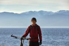 Le touriste monte un vélo avec les roues larges le long du rivage du lac Baïkal photos libres de droits