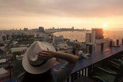 Le touriste observe le beau coucher du soleil sur le dessus de toit de l'hôtel pour Pattaya photographie stock libre de droits