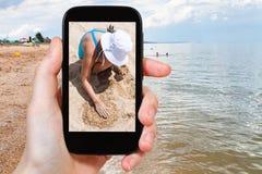 Le touriste photographie la fille jouant avec le sable Image libre de droits