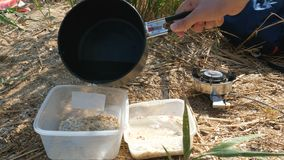 Le touriste prépare la nourriture sur un brûleur à gaz banque de vidéos