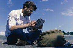 Le touriste regarde la carte Les touristes se sont perdus, s'asseyent regardant sa carte ou guide Photos stock
