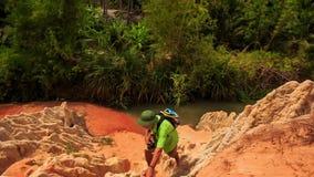 Le touriste s'élève entre les roches de la rivière en parc de Fée-courant banque de vidéos