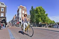 Le touriste sur un vélo de location apprécie Amsterdam Photographie stock libre de droits