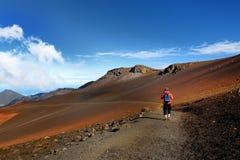 Le touriste trimardant en cratère de volcan de Haleakala sur les sables coulissants traînent image stock