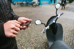 Le touriste va utiliser le scooter électrique par l'application mobile dans le téléphone et l'activer d'une manière distale a Photo stock