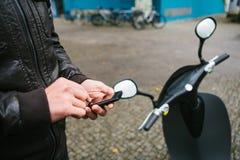 Le touriste va utiliser le scooter électrique par l'application mobile dans le téléphone et l'activer d'une manière distale a Images stock