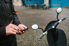 Le touriste va utiliser le scooter électrique par l'application mobile dans le téléphone et l'activer d'une manière distale a Photos stock