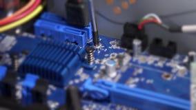 Le tournevis dévissent le boulon sur la carte mère d'ordinateur Travaux de garantie d'ordinateur clips vidéos