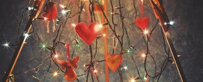 Le trépied en bois, chevalet décoré des lumières de Noël et Han Photographie stock libre de droits