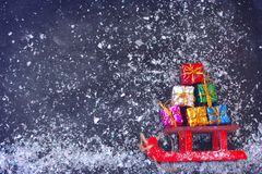 Le traîneau rouge de Noël portent le groupe de boîte-cadeau coloré image stock