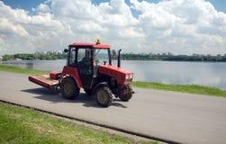 Le tracteur abaisse sur une route contre le paysage de ville images libres de droits