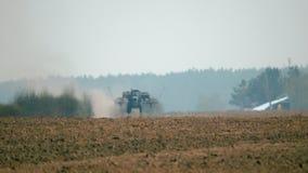 Le tracteur agricole avec le semoir va travailler à un champ sale avec le sol brun par temps chaud et sec banque de vidéos