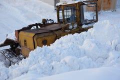 Le tracteur avec le grattoir enlève la neige Image stock
