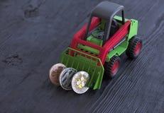 Le tracteur de jouet ratisse la crypto devise de pièces de monnaie photographie stock