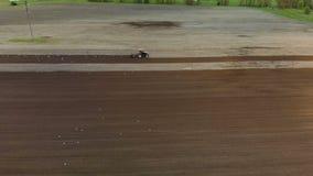 Le tracteur laboure le champ Les oiseaux d'oiseaux volent autour de lui L'encemencement du sol clips vidéos