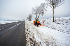 Le tracteur nettoie la route de bicyclette de la neige, paysage d'hiver photographie stock