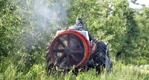 Le tracteur pulv?rise l'insecticide dans des domaines de champ de pommiers photo stock