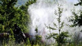 Le tracteur pulv?rise l'insecticide dans des domaines de champ de pommiers photos stock