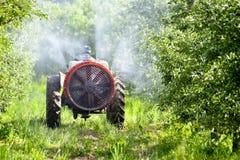 Le tracteur pulv?rise l'insecticide dans des domaines de champ de pommiers image stock