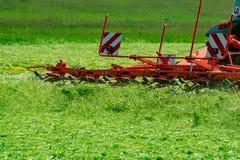 Le tracteur tourne l'herbe sèche image libre de droits