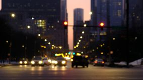 Le trafic brouillé dans la ville la nuit Voitures se déplaçant par une intersection avec des bâtiments de Chicago à l'arrière-pla banque de vidéos