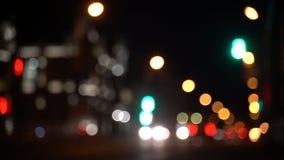 Le trafic brouillé de bokeh sur la route la nuit dans la grande ville banque de vidéos